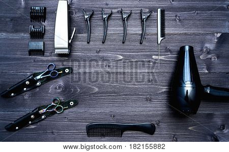 Hairdresser tools on wooden background. Top view on wooden table with scissors hairclips comb clipper and hairdryerl free space. Barbershop manhood concept