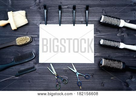 Hairdresser tools on wooden background. Blank card with barber tools flat lay. Top view on wooden table with scissors comb hairbrushes and hairclips with empty white paper free space. Barbershop manhood concept