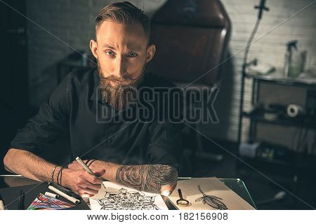 Thoughtful bearded man drawing calligraphic ornaments at table in apartment. Creativity concept. Potrait