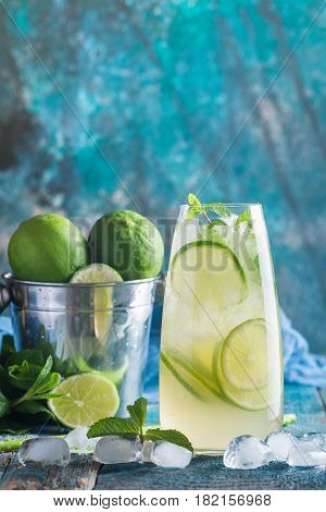 Mojito cocktail with lime and mint in highball glass on blue background