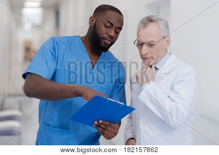 Comparing our experience . Young ambitious African American doctor standing in the hospital while holding folder and sharing opinions with aged colleague