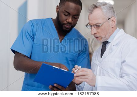Asking experienced colleague. Hardworking young African American doctor standing in the hospital while holding folder and listening to the opinion of the aging colleague