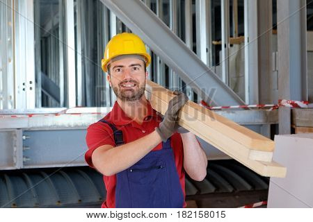 Carpenter worker holding a stack of wooden boards