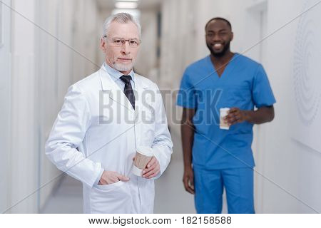 Inspiring colleagues with respect. Handsome experienced senior practitioner standing in the clinic while holding cup of coffee and enjoying break with African American colleague