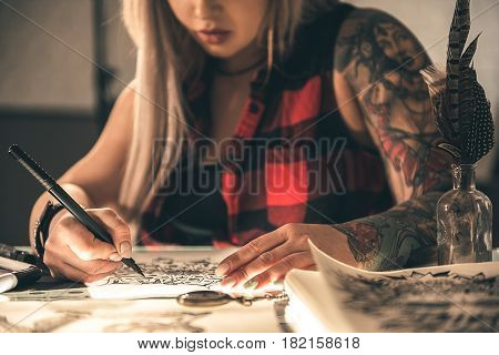 Focus on pen which woman holding in arm. She making tattoo sketch at table. Different equipments for creativity locating on it
