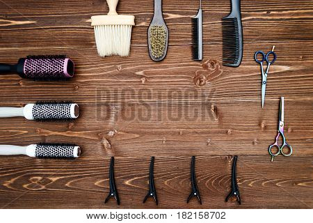 Hairdresser tools on wooden background. Top view on wooden table with scissors comb hairbrushes and hairclips free space. Barbershop manhood concept
