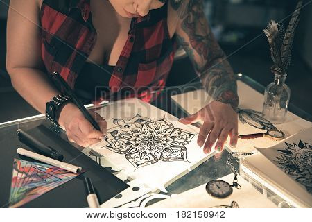 Tattoo master painting sketch at table. Different equipments for creativity situating on it