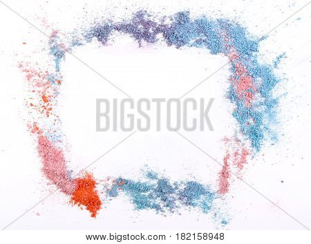 Makeup eyeshadow and blush abstract frame background of pink, blue and coral tones sprinkled on white. Make up and female cosmetics background