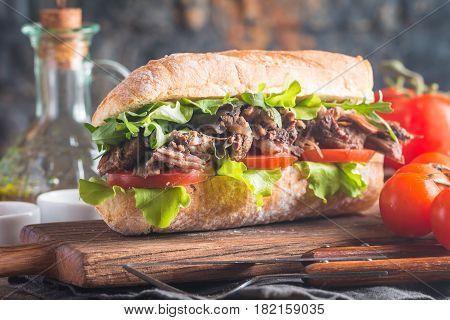 Beef sandwich with tomato and salad on wooden cutting board with ingredients.