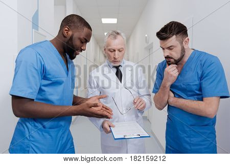 Asking for professional advice. Positive inspired African American intern standing in the hospital while discussing the diagnosis with experienced colleagues and enjoying conversation