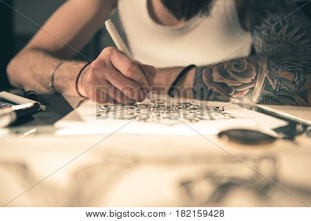 Focus on pen which man keeping in arm. He painting tattoo sketch at table. Picture concept. Close up