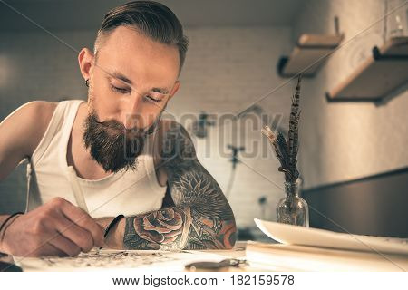 Low angle of calm bearded male drawing image at desk in apartment. Creativity concept. Portrait