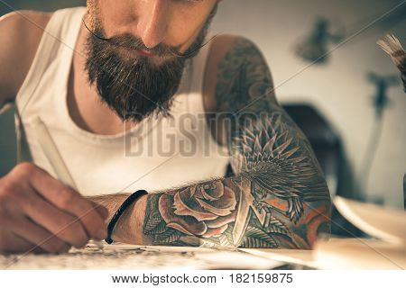 Focus on close up tattoo arm of bearded man creating picture at table