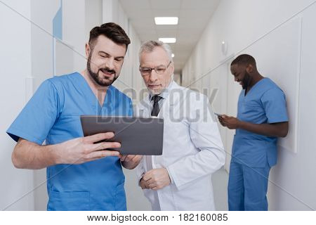 Look at this technical innovation. Involved proficient happy medics standing in the clinic and testing tablet while other colleague using folder in the background