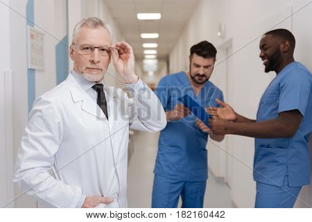 Controlling examination process of interns. Confident smart bearded medic working in the clinic and touching glasses while interns having conversation in the background