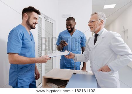 Enjoying everyday checkup at work. Friendly qualified aged physician working in the hospital and checking everyday report while having conversation with colleagues