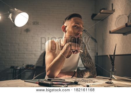 Pensive bearded male painting tattoo pictures. He looking at camera while sitting at table. Portrait