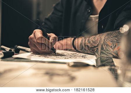 Focus on close up arm of man drawing picture. He sitting at desk in apartment