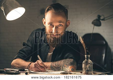 Cheerful bearded male artist painting images at table. He looking at camera with joy