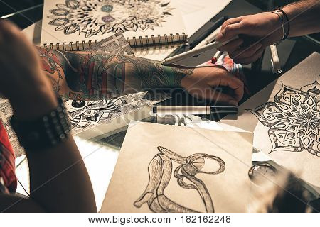 Focus on female hand with tattoo situating on desk near various art pictures. Man pointing at it. Close up