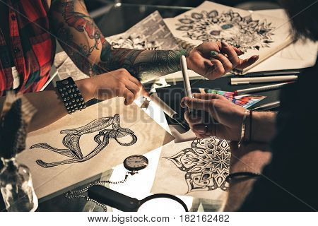 Focus on female hand with tattoo situating on desk. Male telling with her about her picture