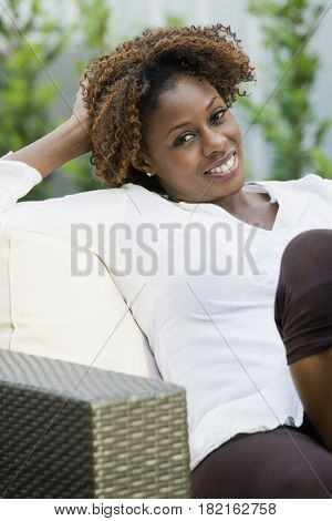 Confident African woman sitting in armchair