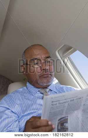 Hispanic businessman reading newspaper on private jet