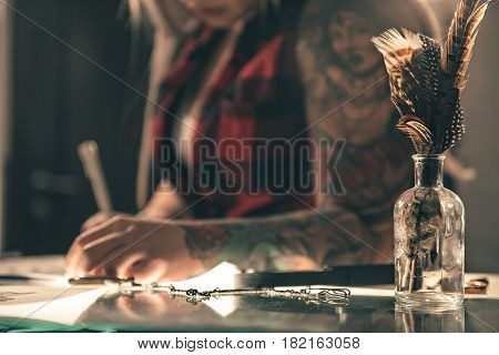 Focus on close up feathers in little glass can for interior. Woman writing while sitting at table. Inspiration concept