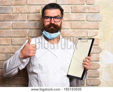 Bearded man long beard. Brutal caucasian doctor or unshaven hipster postgraduate student holding clipboard in medical gown and mask on beige brick wall studio background. Medicine concept