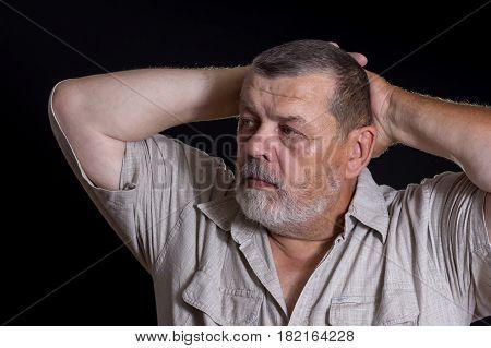 Nice portrait of bearded Caucasian senior man in the darkness