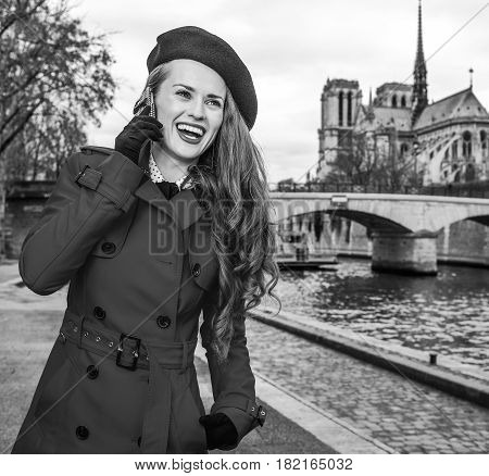Bright in Paris. happy elegant traveller woman in trench coat on embankment near Notre Dame de Paris in Paris France talking on a smartphone