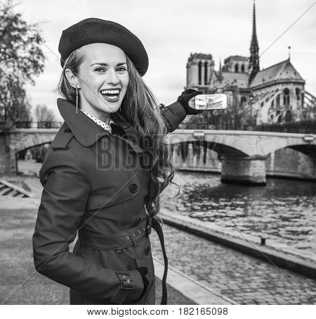 Woman Taking Photo With Mobile Phone On Embankment In Paris