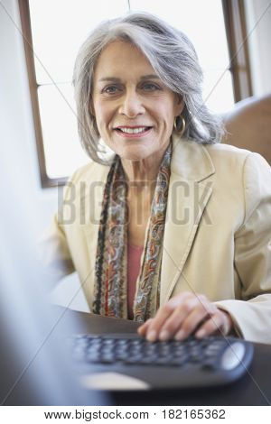Confident businesswoman working on computer at desk