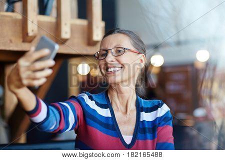Smiley mature woman making her selfie