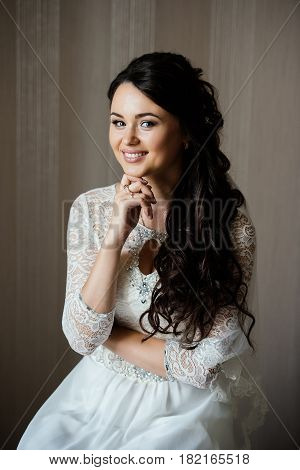 Beautiful young bride in white dress sitting and waiting for the groom indoors. Elegant charming young brunette bride is posing indoors in a wedding dress. Morning the bride