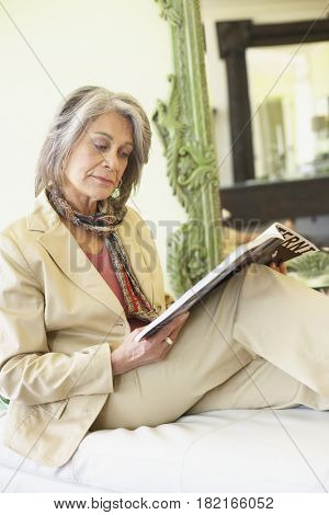 Confident woman relaxing and reading magazine