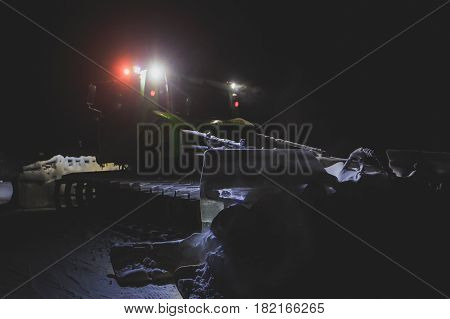 Snowcat bulldozer with multicolored light drives on the slopes and maintenance on the mountains ski resort
