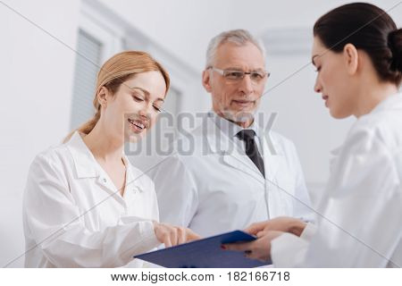Studying diagnosis details. Concentrated professional skilled doctors having checkup in the clinic and exploring diagnosis of the patient while reading information