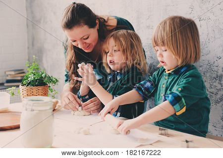 mother cooking with kids in kitchen. Toddler siblings baking together and playing with pastry at home in weekend morning