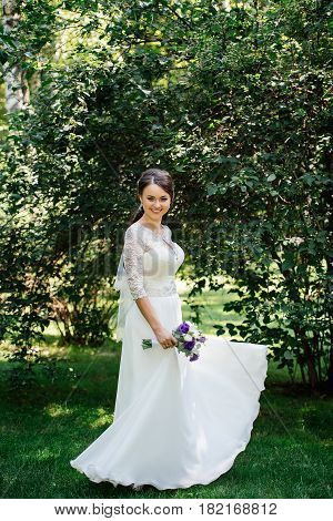 Bride in white dress is spinning in the park. Dress develops in the wind. Happy bride in a wedding dress is spinning.