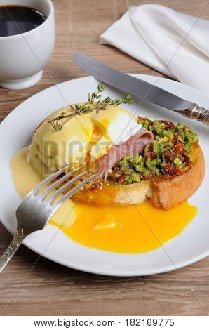 Toasted baguette slice with guacamole ham and eggs Benedict under Dutch sauce