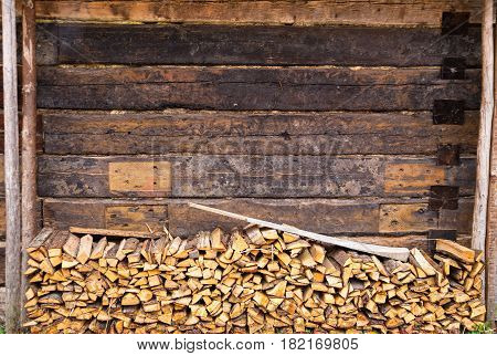 Woodpile And Wooden Wall Of Old Barn Of Brown Color