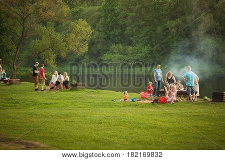 Vilnius Lithuania - May 23 2014: Families are spending their evening in the nature in the public beach on the shore of Neris river in Vilnius.