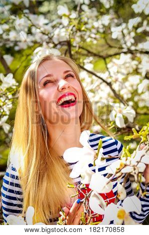 Happy woman in blooming garden. Portrait of spring blonde girl standing outdoor in blooming magnolia garden