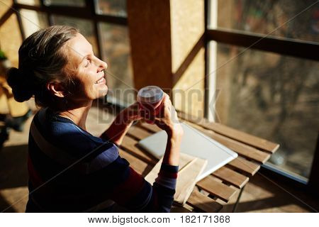 Senior woman with drink taking pleasure in solitude