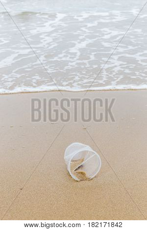 Plastic disposable cup left on sandy beach show environment pollution issue.