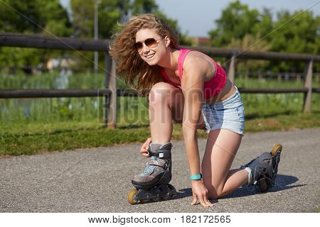 Roller skating sporty girl in park on inline skates. Caucasian woman in outdoor fitness activities.