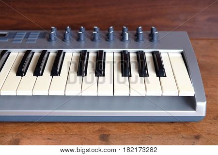 Electronic synthesizer keyboard with many control knobs in silver plastic body on wooden background with small depth of field focused on keys front view close up
