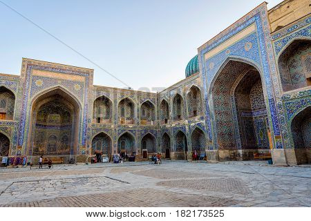 SAMARKAND UZBEKISTAN - AUGUST 27: Visitors at the atrium of the Sher-Dor Madrassah in Registan Samarkand. August 2016