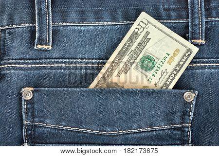 Twenty dollar note in the back pocket of denim trousers